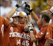 Texas' Michael Hollimon (14) is greeted by teammates Ruben Gonzalez (45) and Eric Sultemeier, second from right, after Hollimon's home run. The Longhorns won their College World Series elimination game Tuesday against Miami, 5-1, in Omaha, Neb.