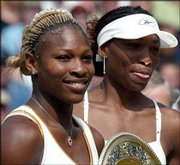 Serena Williams, left, holds her trophy after defeating her sister, Venus, right, in the 2002 Wimbledon final. The sisters were placed on opposite sides of the draw Tuesday for the 2003 event in Wimbledon, England.