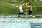 David Shumock, 12, and Cody Williamson, 14, both of Lawrence, hit the water at Lone Star Lake, trying to beat the heat. As the two were frolicking Thursday at the county park southwest of Lawrence, a report was released that showed fecal coliform bacteria levels at the lake were in check.