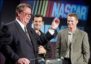 Nextel CEO Tim Donahue, left, holds a phone painted to resemble the NASCAR vehicle of Jeff Gordon, center, as Dale Earnhardt Jr. looks on. NASCAR got a new title sponsor for its top stock car racing series beginning in 2004, signing a 10-year deal with Nextel Thursday in New York.