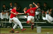 Claremore, Okla., first baseman Trent Short, left, and catcher Eric Bunch scramble into the Lawrence Raiders' dugout in pursuit of a foul ball, which neither caught. The Raiders beat Claremore, 11-1, Thursday in the first round of the Al Ice Memorial Wood Bat Classic at Hoglund Ballpark.