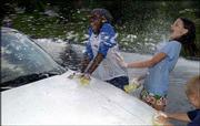 Courtney Griffin, 12, left, and Apollonia Shreders, 12, jump back from a stream of water while washing cars during a Lawrence Parks and Recreation Summer Playground free car wash at Centennial Park. The program's Centennial Park and Deerfield Park campers combined Thursday for a soggy afternoon.