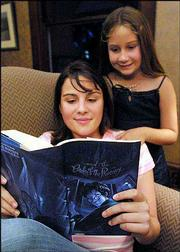 "Kaitlin Webster, 14, reads her copy of ""Harry Potter and the Order of the Phoenix"" in Daytona Beach, Fla. Her sister, Hailey, 8, back, found the book Wednesday at a Walgreens drugstore in Daytona Beach, although the book&squot;s official release is set for 12:01 a.m. Saturday. The store has since taken remaining copies of the book off its shelves."