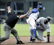 Umpire Larry Poncino, left, calls Minnesota's Torii Hunter, right, safe at second base under the tag of Kansas City shortstop Angel Berroa. The Twins beat the Royals, 16-2, Thursday in Kansas City, Mo.