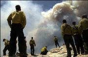 Members of the Flagstaff Hotshots firefighting crew look on as the Aspen Fire crests the ridge west of the Summerhaven community in Tucson, Ariz. The cause of the blaze is under investigation.