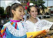 Samantha Romero, 13, left, and Ashley Anguiano, 14, both of Lawrence, fan themselves as they pass out fliers for the dancing programs at the 22nd Annual St. John's Fiesta Mexicana. The two-day fiesta ended Saturday.
