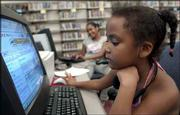 Carleta Nunez, 5, spends some time at a computer in The Zone at the Lawrence Public Library. The Supreme Court ruled Monday that Congress can require public libraries to equip computers with anti-pornography filters. Nunez was with her older sister Pariss Monday at the library.