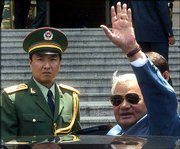 India's Prime Minister Atal Behari Vajpayee waves for the cameras near a Chinese military officer as he leaves the Great Hall of the People in Beijing. Vajpayee is the first Indian prime minister to visit China in 10 years. Vajpayee began his visit Monday in Beijing.