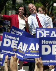 Former Vermont Gov. Howard Dean, center, laughs as he waves to the crowd in Burlington, Vt. Dean made his official entry Monday into the presidential race. At left is his wife, Judy, and behind him is his daughter Ann.