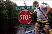 Patrick Scarbrough guides a friend's boat around a stop sign at a corner in North Port, Fla. Scarbrough Monday had just finished helping his in-laws get out of their home, which had 3 feet of water inside.