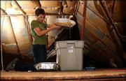 Sarah Finken, a staff member at Achievement Place for Girls, 637 Tenn., pours rainwater into a larger container. The rains Sunday and Monday came in through the home's aging and leaky roof.