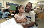 Makenzie Vital, 4, sits with her father, Paul Vital, in a classroom at the Adult Learning Center. Paul Vital took classes at the center and will receive his high school diploma Thursday for completing the General Educational Development program.