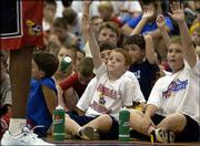 Kansas University basketball campers Jackson Laranc, left, 9, of The Woodlands, Texas, and James Jordan, 9, of Topeka, try to get the attention of former Jayhawk Danny Manning during question time at the camp. Manning was the camp's featured speaker Tuesday.