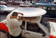 An Iraqi man ties a newly purchased satellite dish to his car in downtown Baghdad. Satellite television, which was banned during Saddam Hussein's regime, is now in big demand in Iraq.