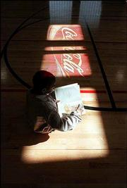Cornelious Leonard, 7, catches some sun in the gym at New York School. The gym's floor does not have a corporate logo painted on it, but that may change if a trend of corporate sponsorship for school activities takes root in Lawrence.
