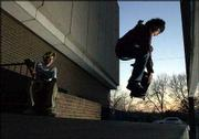 Jake Alvarez, left, 15, waits his turn as his friend Lance Tsosie, 15, ollies off a downtown loading dock. The two Lawrence teenagers skated at dusk Thursday.