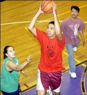 Willie Blacksmith, 16, from the Kickapoo Nation reservation, shoots past counselors Lisa Dixon, left, and Ronnie Brady during a basketball game between students and counselors of an Upward Bound program at Haskell Indian Nations University. About 40 students just completed the month-long program.