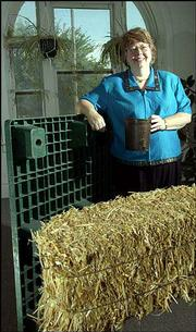 Donna Johnson's company, Pinnacle Technology, 619 E. Eighth St., has developed a means of making plastic using wheat straw. The first manufacturing facility for products made with the material will open later this month in South Africa. Johnson stands next to a shipping pallet and holds a plant pot, both made with 50 percent wheat straw like that visible in the foreground.