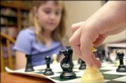 Katie Conard, 8, awaits Gage Buffington as he contemplates the placement of his queen. The two played during a Monday night chess practice.