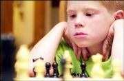 Gage Buffington, 7, Lawrence, studies his opponent's moves during a meeting of the beginners on the Quail Run School chess team. During summer, the group meets every Monday to learn and sharpen skills on the chessboard.