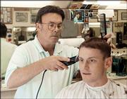 Mike Amyx, left, gives Josh Boydston, Topeka, a trim on Tuesday.