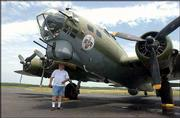 Gerald Thompson, Lawrence, gets a closer look at a B-17 bomber at Lawrence Municipal Airport. The B-17 will join other vintage aircraft on Monday in an air parade in Lawrence as part of the Dole Institute of Politics dedication at Kansas University. Thompson was at the airport Wednesday.