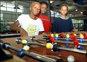From left, Markcus Sanders, 10, Donshae West, 10, and Julyan Wilson, 10, play foosball at the East Lawrence Center. The group avoided heat Wednesday by playing games inside the rec center.