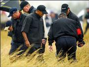 Golfer Tiger Woods, center, searches for his ball in the rough with course officials at Royal St. George's during the first round of the British Open. Woods shot 2-over 73 Thursday in Sandwich, England.