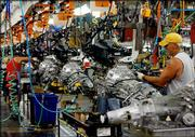 Steve Pittman, foreground, a General Motors Corp. employee from Wellston, Okla., works on the engine assembly line at the GM plant in Oklahoma City in this June file photo. General Motors said Thursday that it had earned $901 million in the April-June quarter, down 30 percent from a year ago, but still ahead of Wall Street expectations.