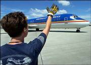 Midwest Airlines employee Lisa Hornbacher, 32, directs a DC-9 departing from Milwaukee's Mitchell Field and bound for Atlanta. Midwest Airlines will avoid filing for bankruptcy protection after it secured concessions from workers and agreements to reduce debt and lease payments on its airplanes, company officials said late Wednesday.