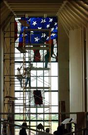 Workers with Stained Glass Overlay, of Roseville, Minn., climb a scaffold at the Dole Institute of Politics to install 4-foot-by-4-foot glass panels making an American flag.