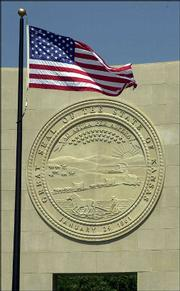A 14-foot replica of the Kansas state seal graces the front wall of the Dole Institute of Politics. The seal, made from four sections of colored cast concrete, was financed by a $50,000 gift from the Dane G. Hansen Foundation.