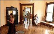 In foreground from left, Amelia Weil, 10, Lawrence; Ethan Piekalkiewicz, 5, Houston; and Weil's mother, Malika Lyon, Lawrence, attend an open house at the remodeled home of Serina Hearn and Tony Backus at 1121 Ohio. The house was dilapidated in fall 2002, but restoration of the home has returned it to near original condition. Standing in background during Sunday's open house are Sam Fields, Lawrence, left, a former tenant in the house for 13 years, and Jarek Piekalkiewicz, Lawrence, a friend of the homeowners.