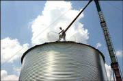 Hot weather doesn't bother Frankie Foreman 46, of Helena, Ark., as he tops off a grain bin at a property in northeast Lawrence. Foreman travels with his wife and daughter, and they are in Lawrence as he seeks work such as the grain bin job he completed Sunday.