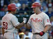 Philadelphia's Bobby Abreu, left, congratulates Jim Thome after Thome's two-run home run. The pair of RBIs were the 1,000th and 1,001st in his career and helped propel the Phillies past the Chicago Cubs, 3-0, Wednesday in Chicago.