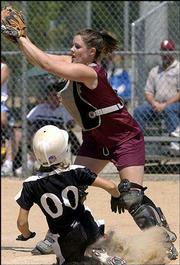 Lawrence phenix catcher Brooke Abney, right, waits for a throw against Tuttle Magic (Okla.). The 14-under Phenix lost, 7-4, Thursday at an AFA tournament at Clinton Lake Softball Complex.