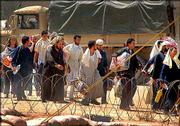 Iraqi prisoners of war walk toward the gates of Camp Bucca in Umm Qasr, southern Iraq before being released by U.S. troops in this May 6 file photo. The military has charged four U.S. soldiers from a Pennsylvania-based Army Reserve unit with abusing prisoners of war in Iraq. The soldiers and their families deny the accusations.