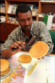 Girmai Misgna, an analyst for the Kansas Geological Survey on Kansas University's west campus looks over some pancakes Friday, to see if they resemble Kansas in any way. A team of researchers from Texas and Arizona recently reported that Kansas was as flat as a pancake.