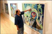 "Robert Price, a Kansas University art professor, hangs his new show called ""Sky Mudras: Paintings by Robert Price"" at the Ann Evans Gallery in the Lawrence Arts Center, 940 N.H. The paintings will be on view through Aug. 27."