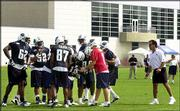 Tennessee coach Jeff Fisher, right, listens to the play being called during training camp. The Titans were practicing Saturday at their headquarters in Nashville, Tenn. The 80,000-square-foot building behind the players contains the team offices, meeting rooms, locker room, weight room and dining facility. The Titans are just one of 13 teams holding training camp at their headquarters.