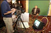 Kansas university football coach Mark Mangino, seated, prepares to be filmed for a commercial for a television station during Big 12 Football Media Day. Mangino recorded the bit Wednesday at the Downtown Marriott in Kansas City, Mo.