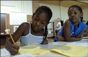 Imani White, 8, left, fills out a form to enroll in the Boys and Girls Club of Lawrence after-school program with her sister Tiani, 6, right. The sisters were going through enrollment Wednesday at Pinckney School with their mother, Ambe Dowdell-White, Lawrence. Both girls attended Riverside School last year.