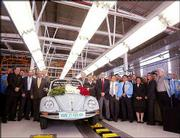 Workers crowd around the last VW Beetle as it rolls off the production line at VW's Puebla, Mexico, plant. The car, which rolled off the line Wednesday, will be sent to a museum in Wolfsburg, Germany. The 300 employees working on the bug assembly line will be reassigned to other departments at the factory, which also produces Jettas and the modern new Beetle.