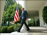 President Bush arrives for a news conference in the Rose Garden of the White House. Bush on Wednesday accepted personal responsibility for a controversial portion of last winter's State of the Union address dealing with claims that Saddam Hussein was seeking nuclear material in Africa.