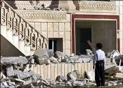 An Iraqi boy looks at the house where Odai and Qusai Hussein were killed last week in a firefight with U.S. troops in Mosul, Iraq. The house is being demolished, officials said, in part to prevent people from squatting in the building. After a tape purported to be from Saddam Hussein was aired this week, Iraqis began to accept the fact that the former dictator's sons were indeed dead.