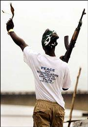 A government fighter, with a ju-ju magic charm in one hand and an AK-47 in the other, taunts rebels across the Mesurado bridge in the Liberian capital, Monrovia. Government and rebel forces exchanged small arms and mortar fire Wednesday despite a proclaimed ceasefire.