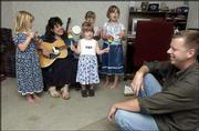 Christian humorist Linda Havenor, second from left, and her children, Natalie, 5, Audrey, 2, Olivia, 6, and Kayla, 7, perform a song for Warren Havenor, right. Linda and Warren homeschool their children.