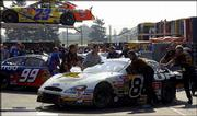 Dale Jarrett's crew pushes his car into the garage after practice. The team raced Friday in Indianapolis.