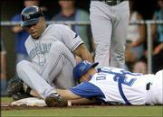 Royals catcher Mike DiFelice, right, dives into first base as he tries to tag out Tampa Bay's Carl Crawford in the first inning. DiFelice was backing up a play after Carlos Febles fielded a grounder and threw the ball past first. Crawford was safe on the play Friday in the Devil Rays' 9-6 victory in Kansas City, Mo.