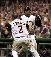 Pittsburgh's Tike Redman, right, is greeted by Jack Wilson after scoring from third with the game-winning run on a single by Jason Kendall in the bottom of the ninth inning. Redman had tied the game with a two-run triple, his second triple of the game, as the Pirates won, 12-11, Friday in Pittsburgh.
